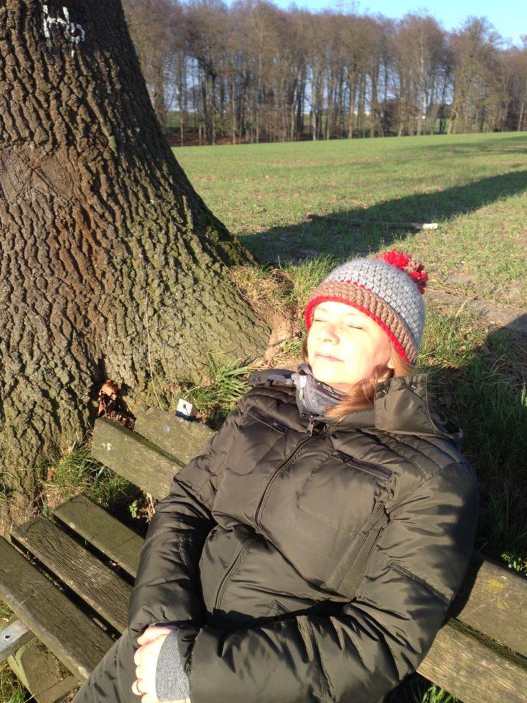 Dagmar sitzt auf einer Bank und sonnt sich