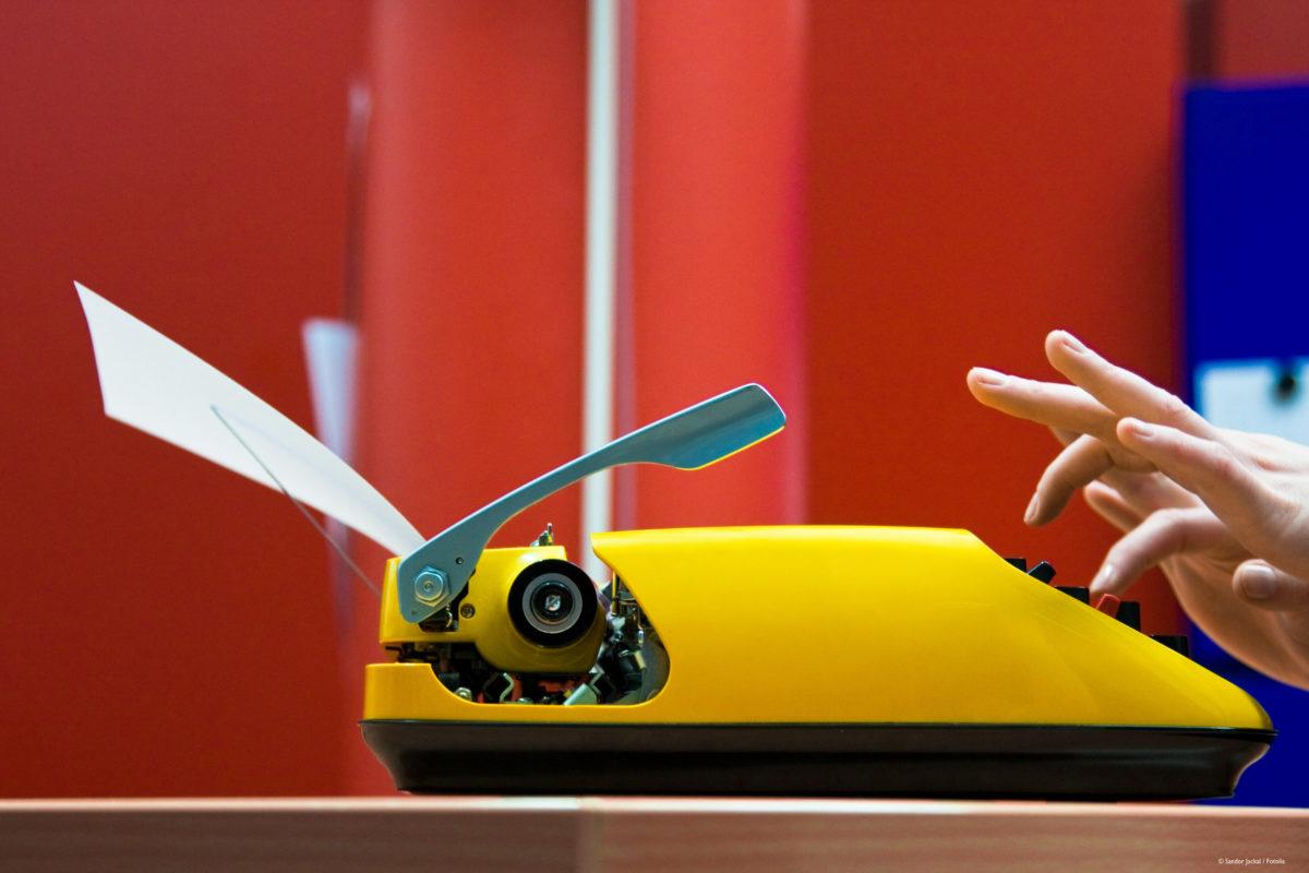 Schreiben auf einer gelben Schreibmaschine